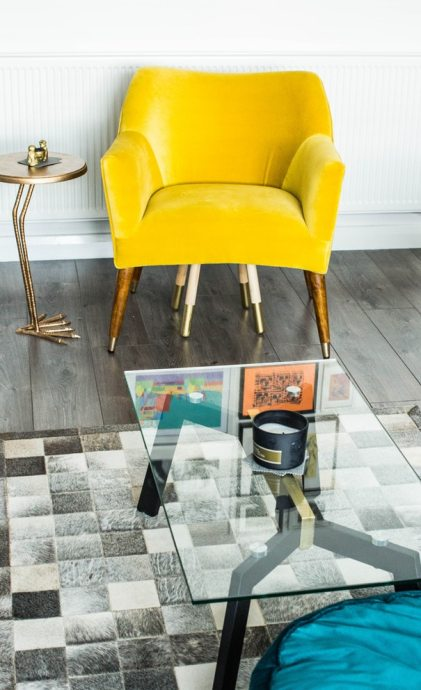 living room space with yellow arm chair and glass table